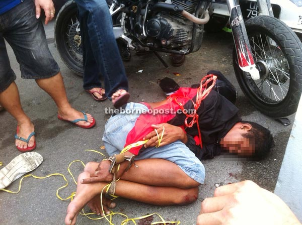 Snatch thief detained by the public. Image from The Borneo Post Online.